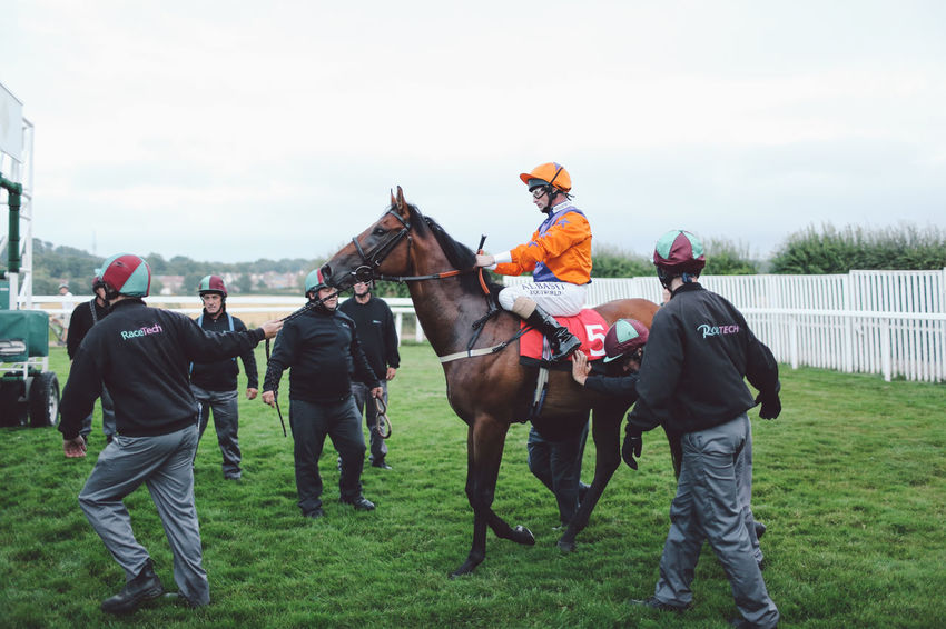 Countryside Domestic Animals Epsom Downs Racecourse Full Length Gate Gates Horse Horse Racing Horse Riding Horseback Riding Jockey Jockeys Leisure Activity Livestock Mammal Men Person Race Race Course Rear View Riding Sky Start Transportation Working Animal