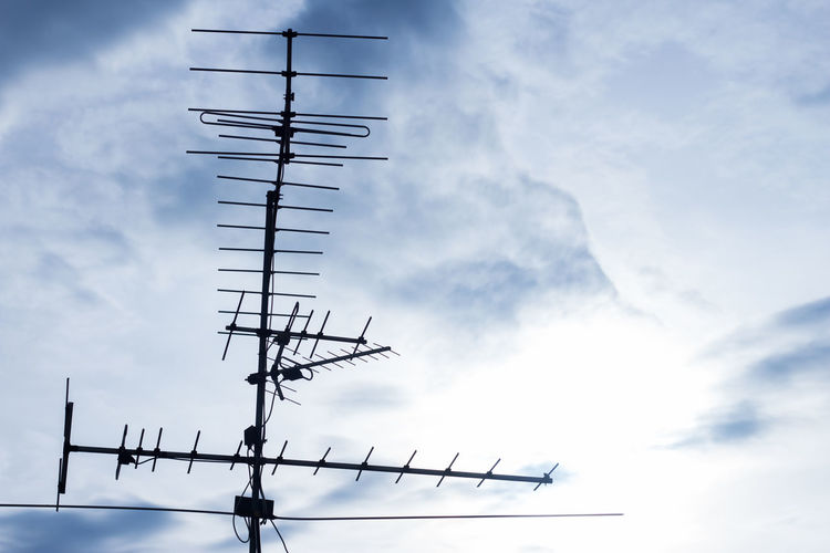 Low angle view of silhouette communications tower against sky