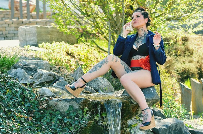 Full length of woman sitting on rock at ornamental garden