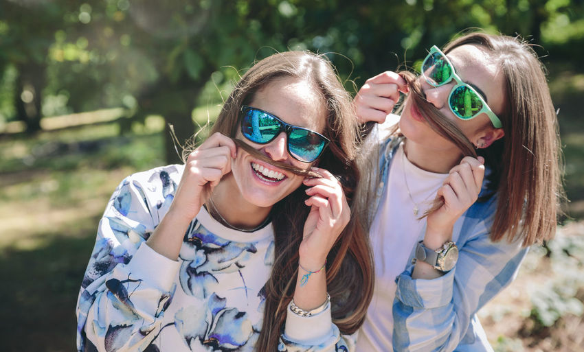 Portrait of funny women with sunglasses doing moustaches with their long hair and laughing. Relax and leisure time concept. Autumn Friends Fun Funny Green Horizontal Moustache Nature Woman Caucasian Emotion Female Forest Friendship Girl Hike Leisure Lifestyles Long Hair Mountain Outdoors Smile Summer Sunglasses Two People