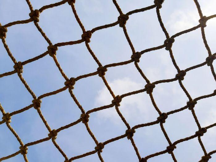 Football goal post netting against blue sky