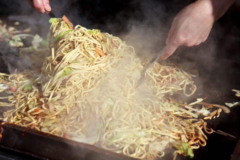 Cropped hand of man preparing noodles food