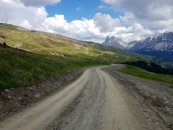 Dirt road by mountains against sky