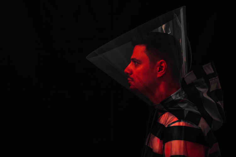 Profile View Of Man Wearing Protective Collar Against Black Background