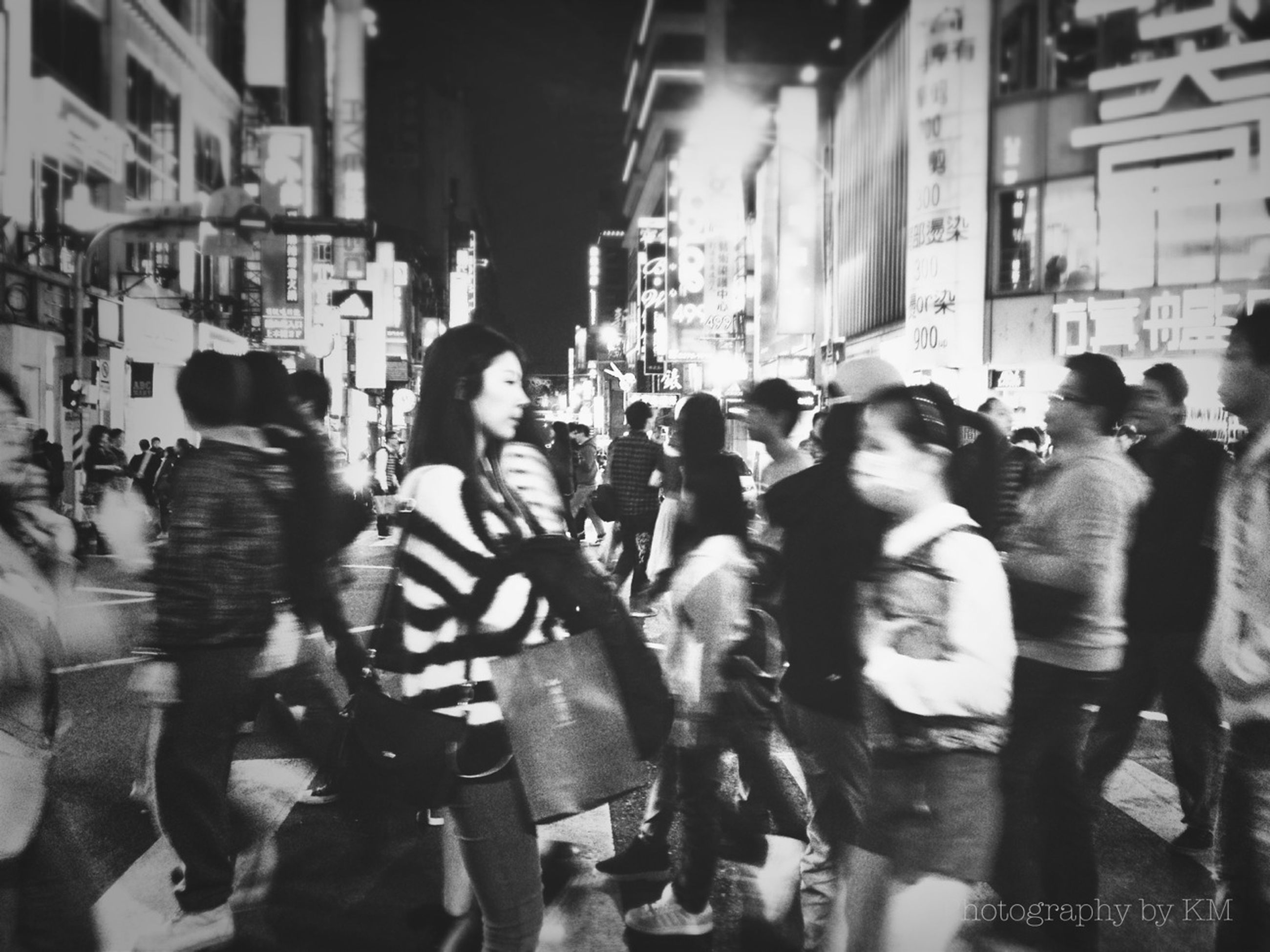 large group of people, men, person, lifestyles, crowd, street, leisure activity, city life, city, building exterior, walking, built structure, mixed age range, architecture, city street, togetherness, medium group of people, road, illuminated