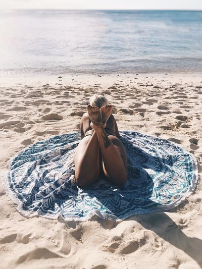 Rear view of woman lying on blanket at beach