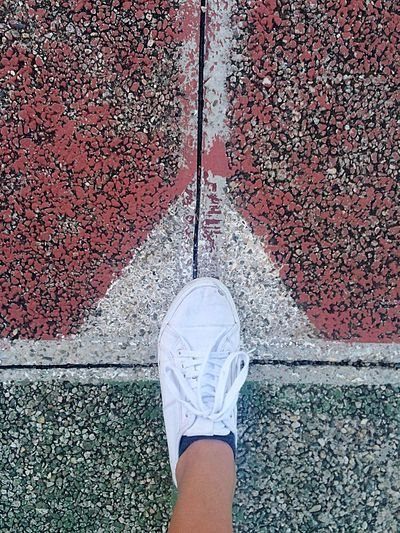 High level view of tennis shoe on asphalt pitch floor