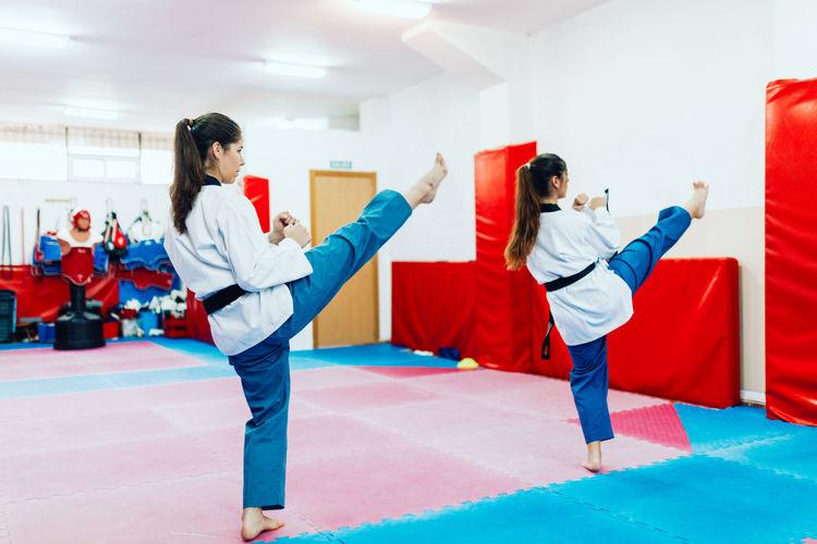 Rear view of people doing taekwondo