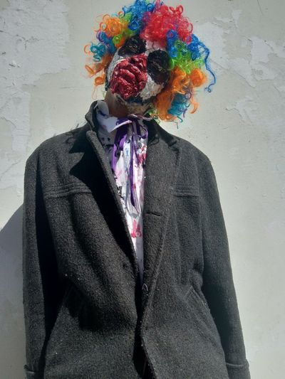 Young man in clown make up standing against wall