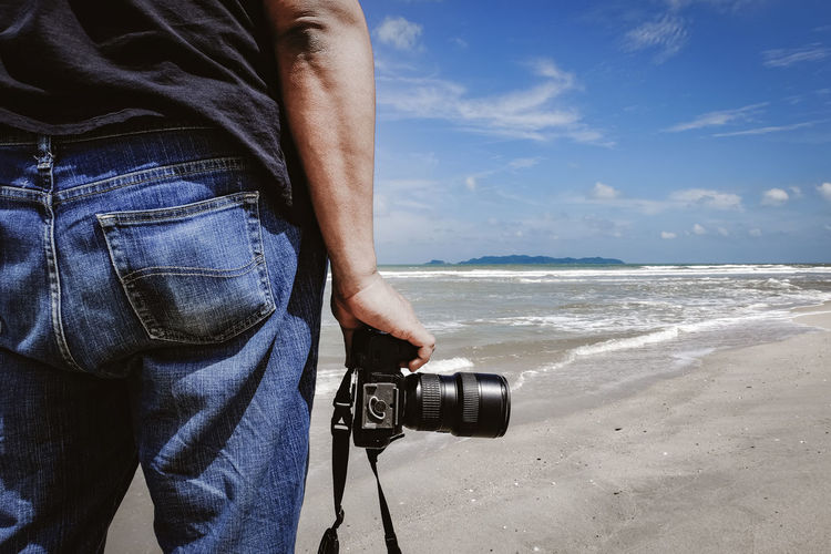 Midsection of man with camera standing at beach against sky