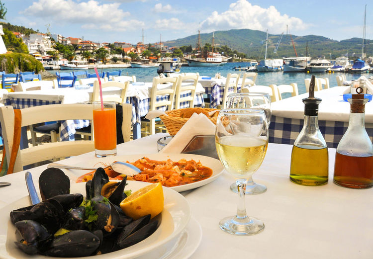 Food on table at restaurant by sea against sky