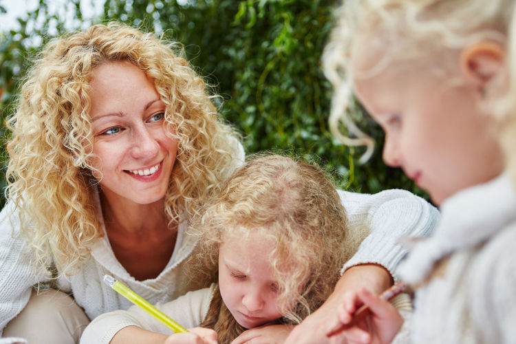 Smiling mother with kids outdoors