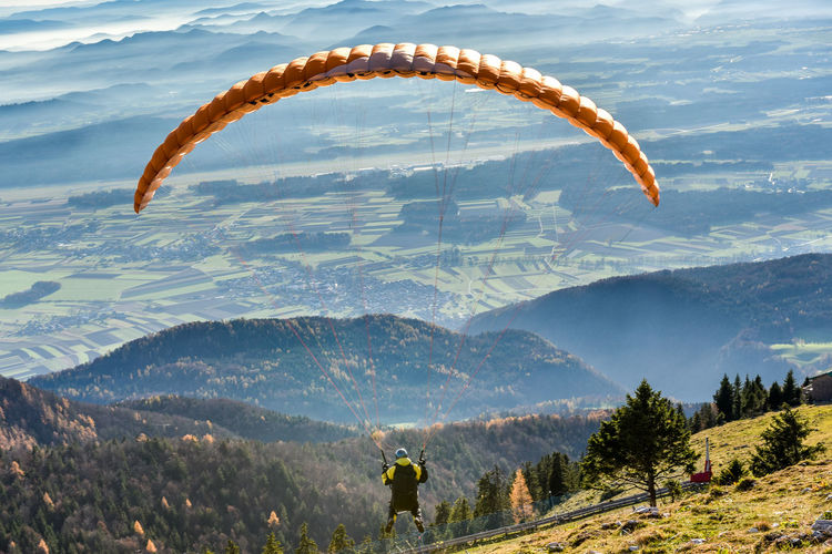 High Angle View Of Person Paragliding Over Mountains