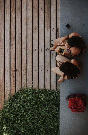 Friends chatting during a party Wood - Material People Directly Above Front Or Back Yard Day Outdoors Summer Girls Sitting Women Breathing Space