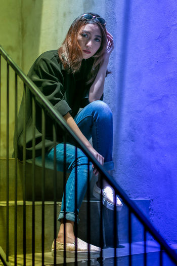 Portrait of young woman sitting on staircase against wall