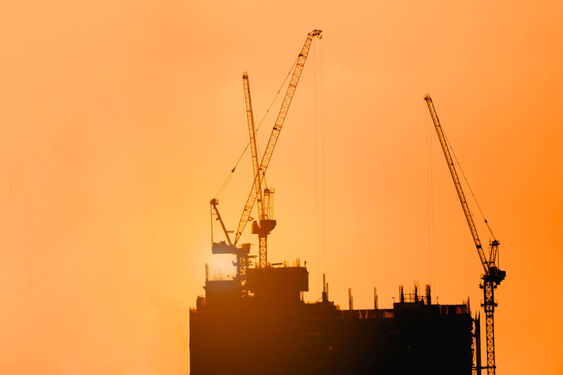 Cranes at construction site against clear sky during sunset