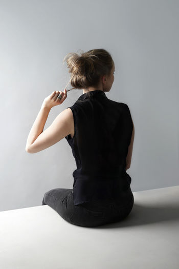 Rear View Of Woman Sitting Against Gray Background