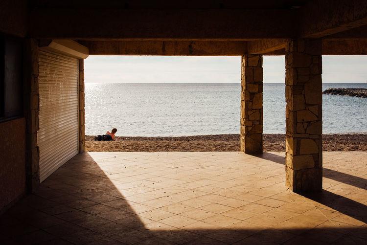 Teenage boy relaxing on sand against sea