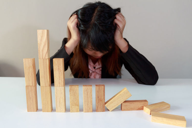 Frustrated Woman With Wooden Blocks On Table