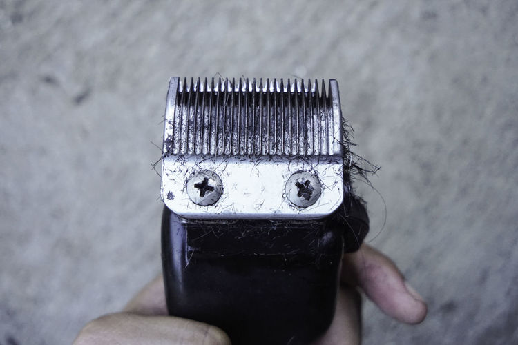 Cropped hand of man holding electric razor with hairs