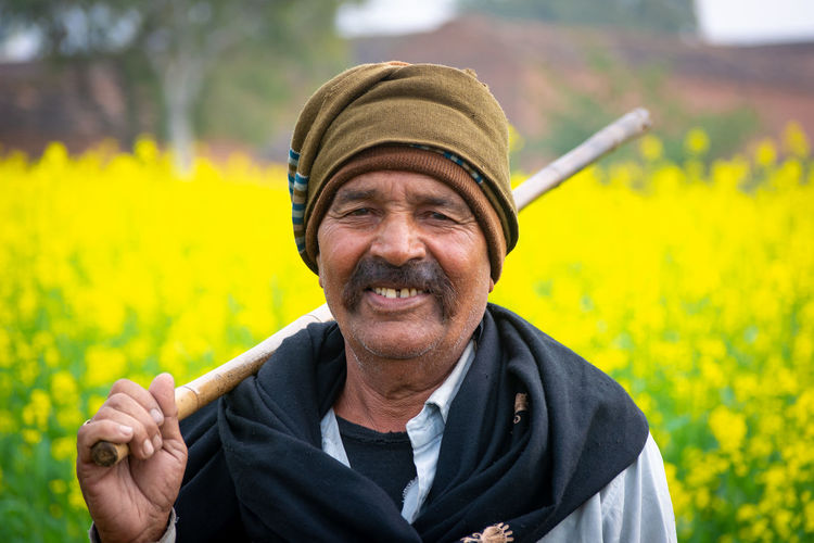Portrait of smiling man on yellow field