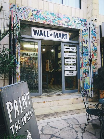 Wall Mart Palestine Israel West Bank Store Business Finance And Industry Communication City Text Western Script Architecture Built Structure Store Sign Protestor Street Art Entryway Open Sign Information Sign Aerosol Can Graffiti Spray Paint Welcome Sign