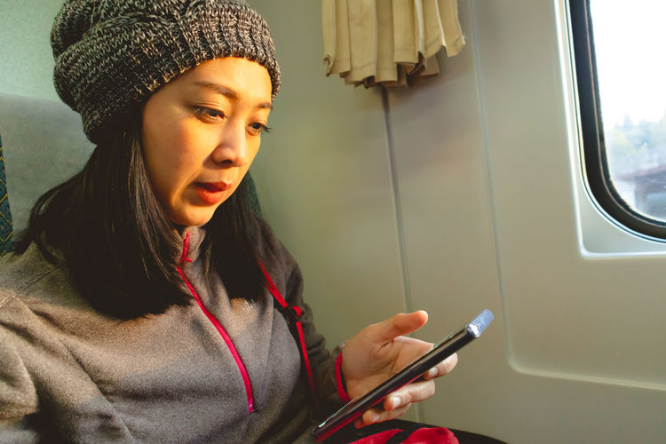 Midsection of woman using mobile phone while sitting in bus