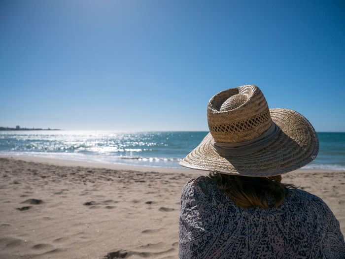 Rear view of woman wearing sun hat at beach against clear blue sky