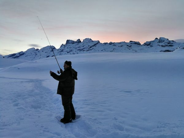 early bird hunts early fish Snow Winter Mountain Cold Temperature Landscape One Man Only Frozen One Person Outdoors Standing Adult Mountain Range Travel Destinations Adventure