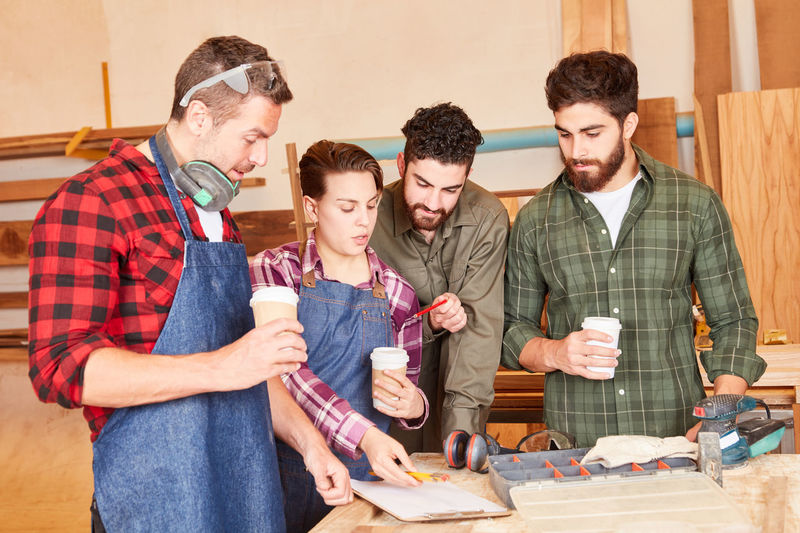 Cheerful carpenters holding coffee cup at workshop