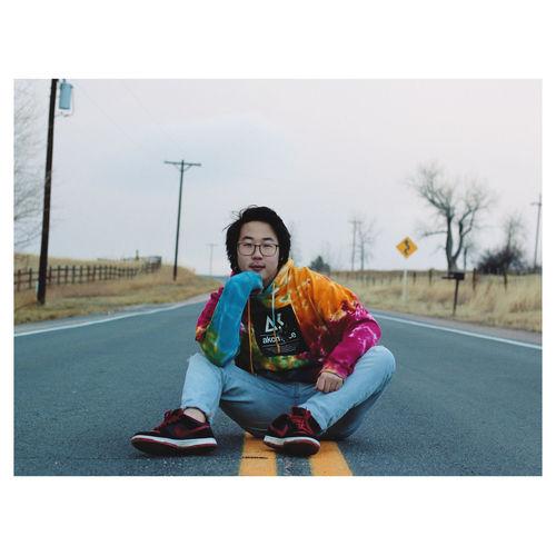 Portrait of teenage girl sitting on road against sky