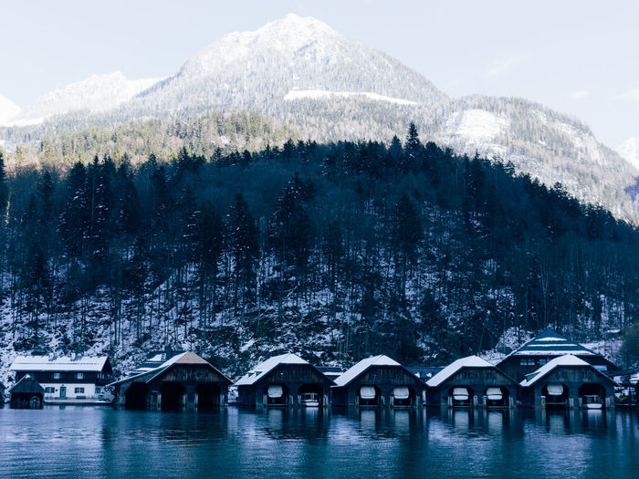 Houseboats in river against snowcapped mountains