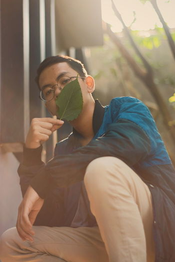 Portrait of young man holding leaf over mouth while crouching outdoors