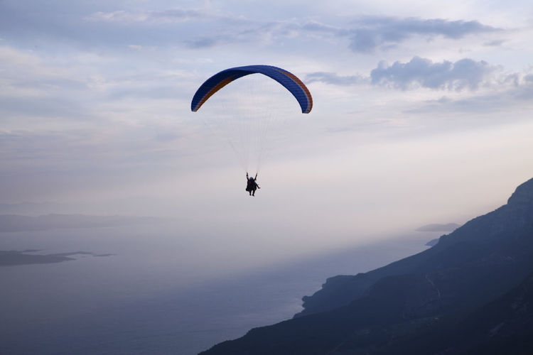 Man Paragliding Against Sky