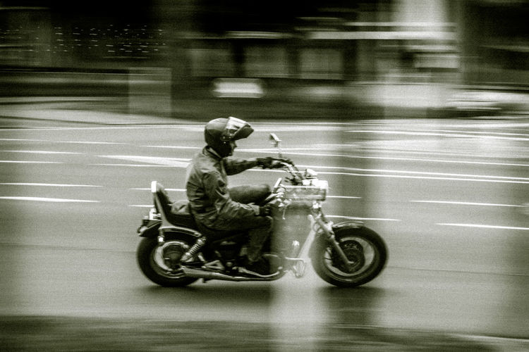 Side view of a person riding motorcycle on road