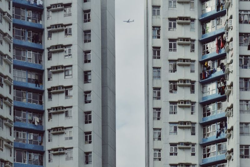 Low angle view of airplane amidst residential buildings