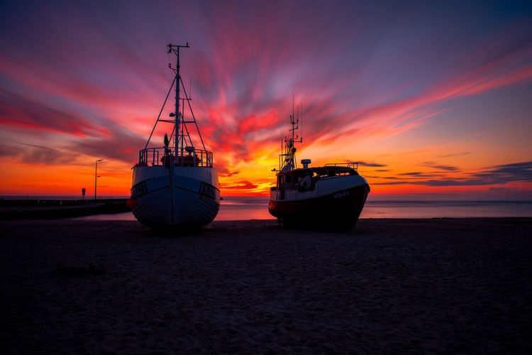 Sailboats moored on sea against romantic sky at sunset