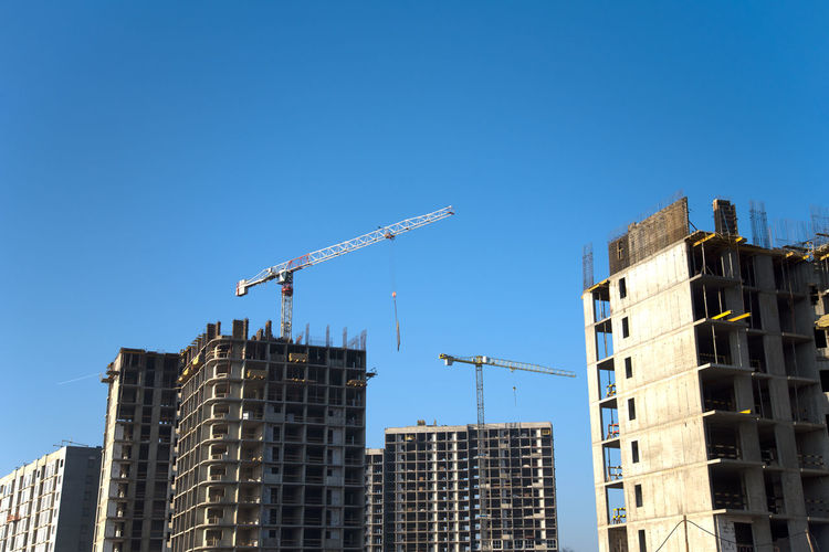 Low angle view of crane and buildings against clear blue sky