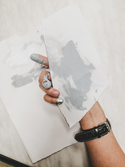 High angle view of human hand holding paper