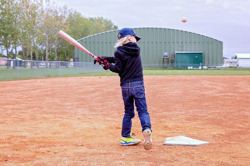 Full length of girl playing baseball at field