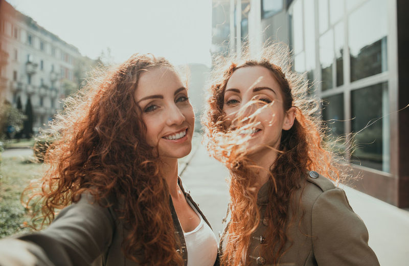 Portrait of smiling young women doing selfie outdoors