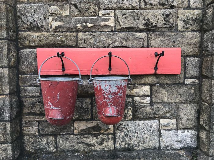 Old buckets hanging against stone wall