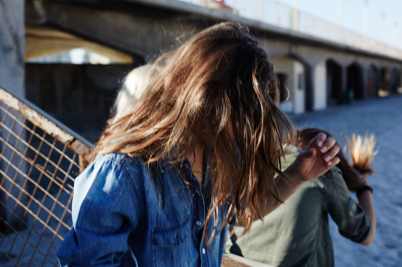 Architecture Blond Hair Building Exterior Built Structure Casual Clothing Close-up Day Denim Jacket Focus On Foreground Lifestyles Long Hair Medium-length Hair One Person Outdoors People Real People Rear View Warm Clothing Young Adult