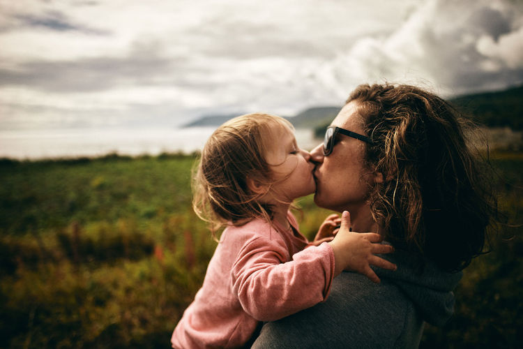 Side view of mother kissing daughter while standing on land