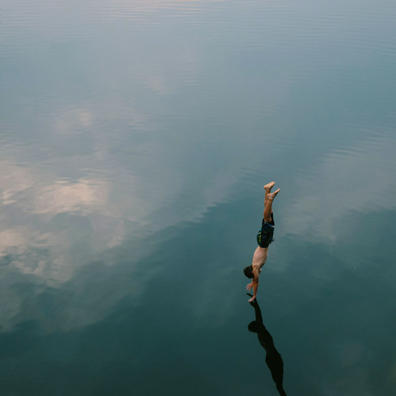 High angle view of man diving into calm lake