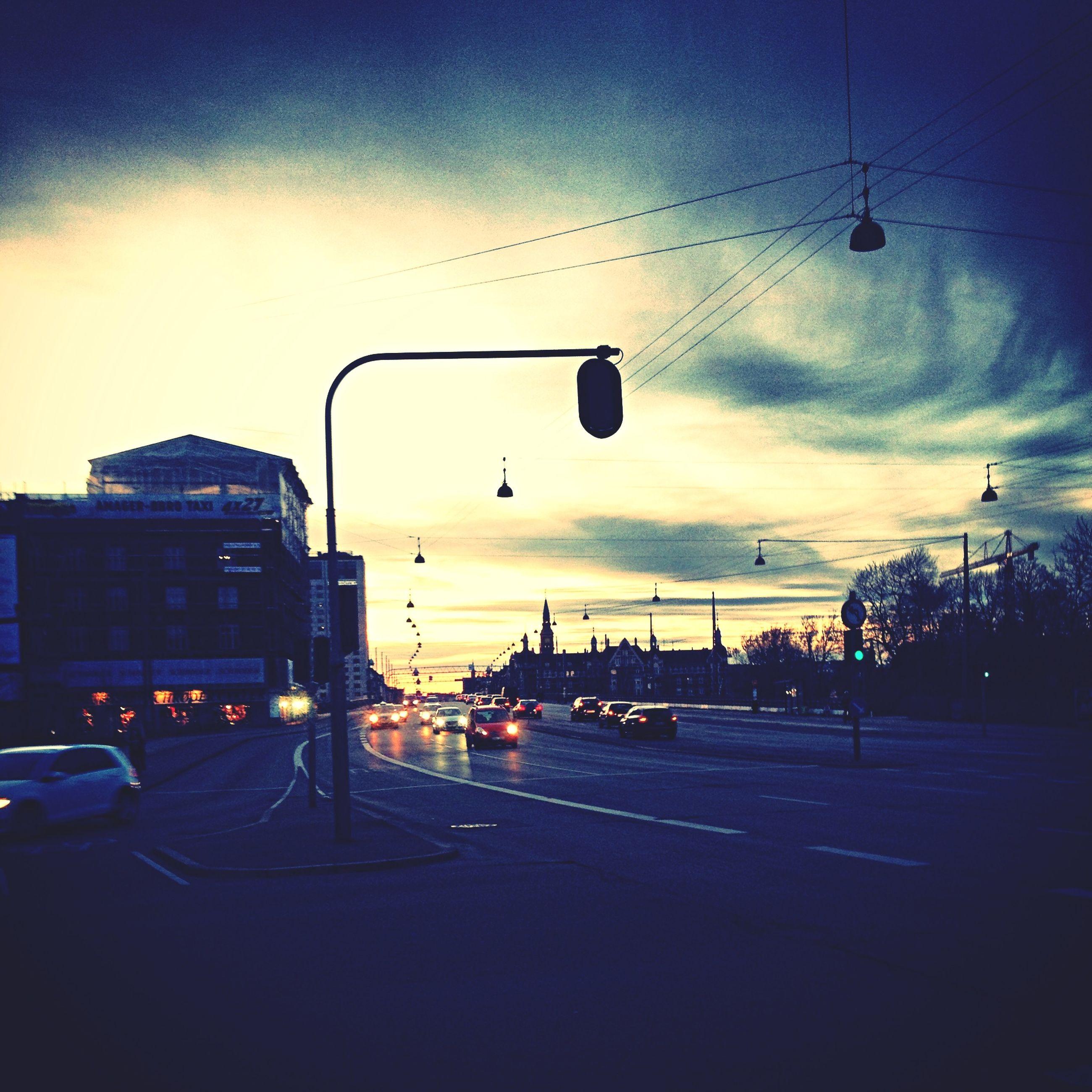 transportation, car, street light, land vehicle, sky, illuminated, mode of transport, road, street, sunset, building exterior, built structure, traffic, cloud - sky, architecture, lighting equipment, city, dusk, city street, road marking
