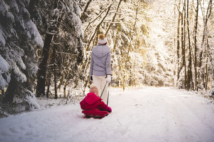 Woman walking on snow covered land
