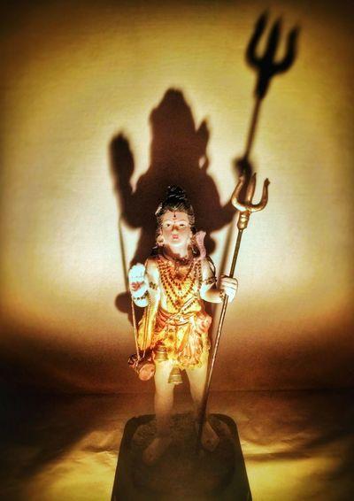Close-up of female statue against illuminated light