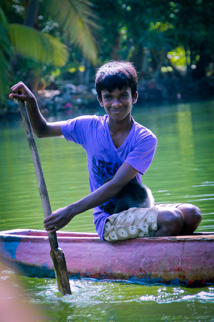 looking at camera, water, one person, portrait, leisure activity, casual clothing, young adult, front view, real people, sitting, smiling, young men, lifestyles, happiness, child, full length, day, emotion, teenager, outdoors, adolescence, teenage boys, purple, human arm