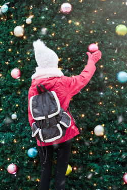 Young girl standing at front of big Christmas tree decorated with colorful balls. Teenager girl is wearing warm clothes, scarf and wool cap on a cold winter day Girl Christmas Decoration Ball Ornament Holiday Winter Wintertime Female Outdoors Cold Temperature Wintery Snowing Tree Joy Joyful Green Lights Merry Merry Christmas! Pine person Teenager Snowy Tradition